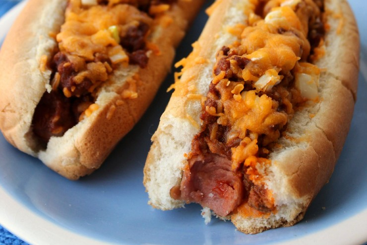 Chili Cheese Dogs are an American Classic - Hotdogs Smothered in Chili Con Carne, Cheddar Cheese and Onion.