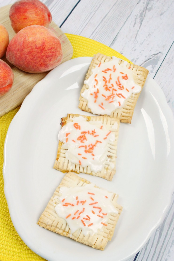 These Peach Pop Tarts are a treat your whole family will enjoy for breakfast or desert. Little hand pies filled with peach preserves and topped with icing - they are a taste of summer you can enjoy all year long for a special treat!