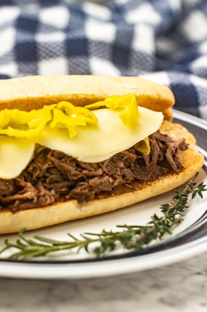 The best slow cooker Italian Beef recipe made with chuck roast, seasonings & pepperoncini. Flavourful, tender beef for sandwiches!