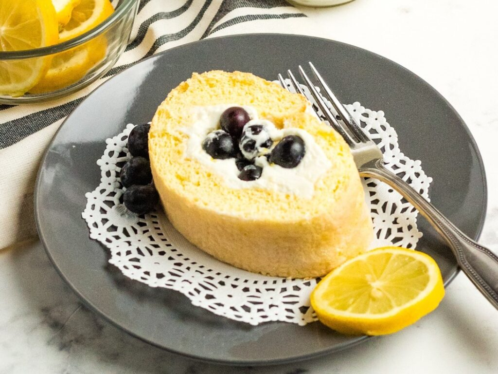 Whipped cream cheese frosting & fresh blueberries fill this Blueberry Lemon Cake Roll (Swiss Roll) a delicious dessert that gets rave reviews!