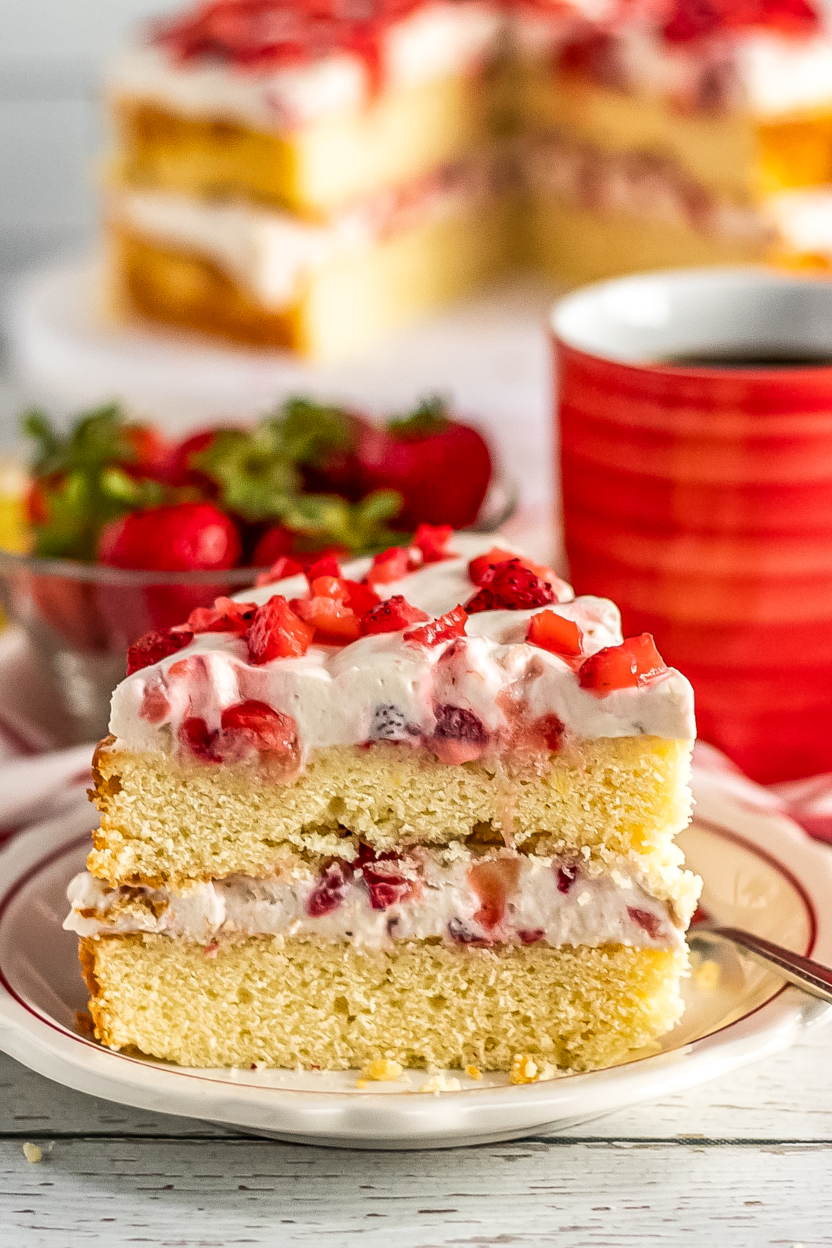 An, easy recipe for a strawberry banana layer cake with layers of creamy whipped cream frosting made with fresh bananas and strawberries.