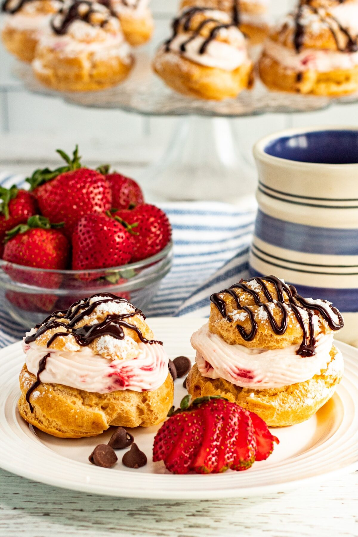 These Strawberry Cream Puffs feature a light, flaky pastry filled with strawberry whipped cream, topped with a chocolate ganache drizzle.