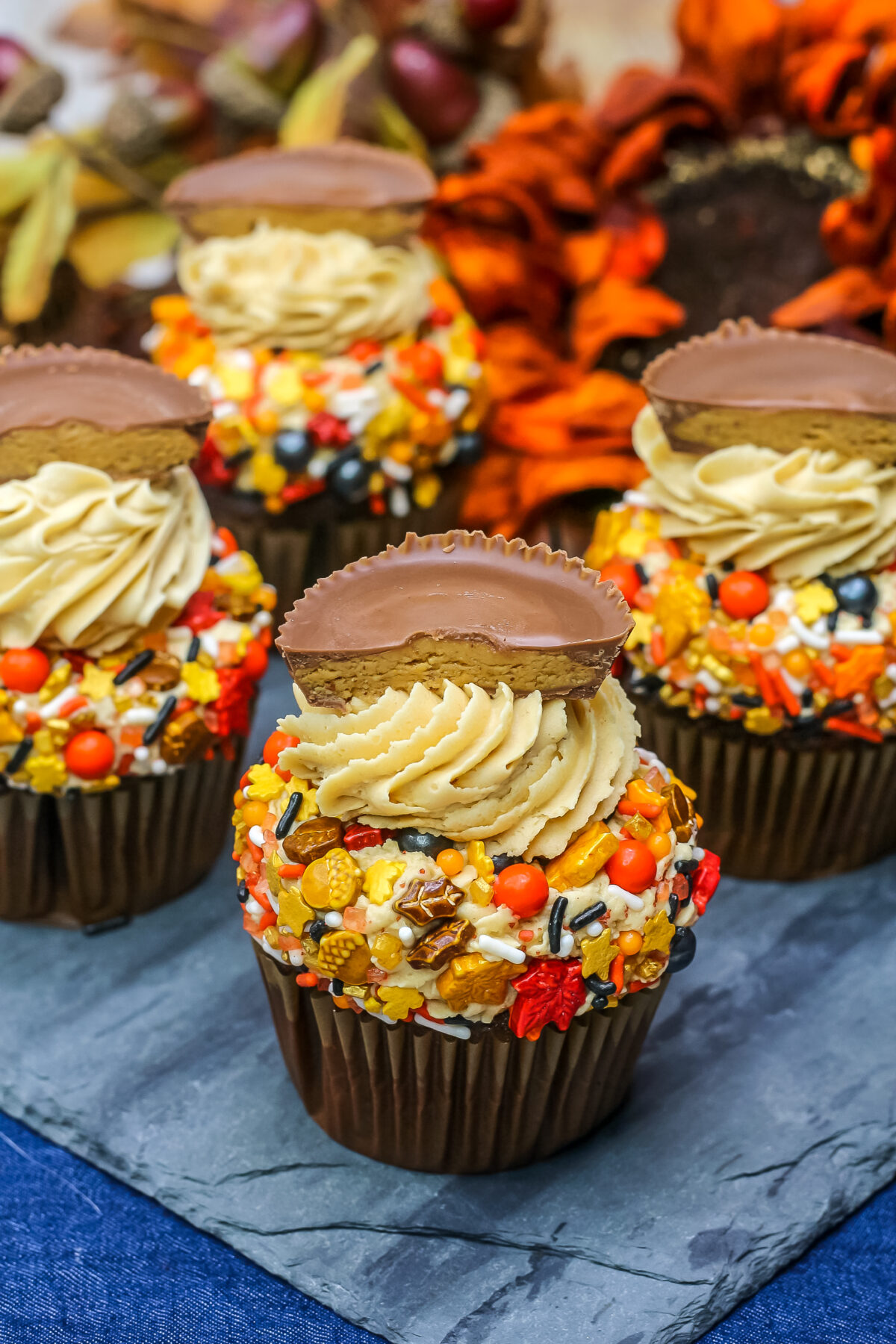 This chocolate cupcakes with peanut butter frosting recipe features a rich chocolate cake, creamy frosting, cute sprinkles and a Reese's cup.